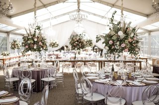 wedding-reception-tent-lavender-purple-table-acrylic-chairs-greenery-pink-flowers-chandeliers