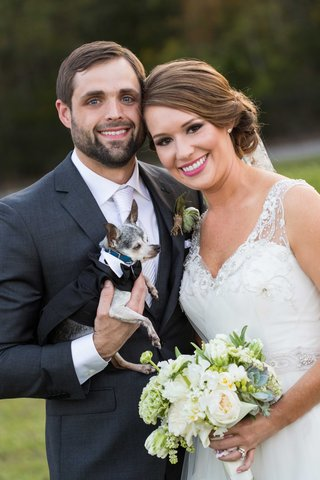 bride-in-nardos-iman-wedding-dress-with-rustic-bouquet-and-groom-in-grey-suit-with-little-chihuahua