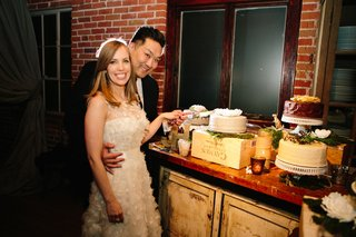 bride-and-groom-cut-into-one-layer-cake-at-dessert-display