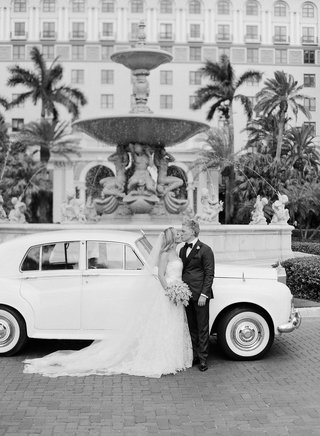 black-and-white-photo-of-bride-and-groom-in-front-of-classic-white-car-in-front-of-the-breakers