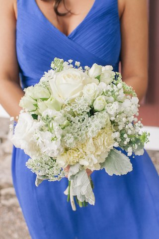 bridesmaid-in-blue-holding-white-flowers-and-greenery