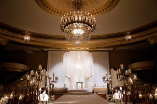 ballroom-wedding-ceremony-candelabra-decorations-white-flowers-candles-white-chuppah-on-stage