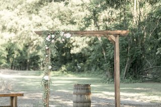 wedding-ceremony-arch-flowers-on-one-side-wood-barrel-in-center-alter-raw-wood-details