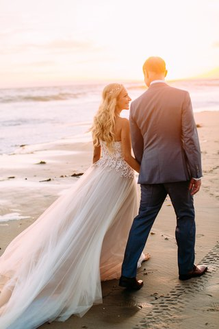 wedding-portrait-photo-ideas-couple-walking-on-beach-bride-with-long-hair-curls-custom-trish-peng