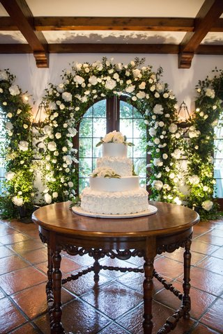 white-wedding-cake-with-fresh-flowers-on-spanish-tile-wood-table-greenery-archway-wood-beams