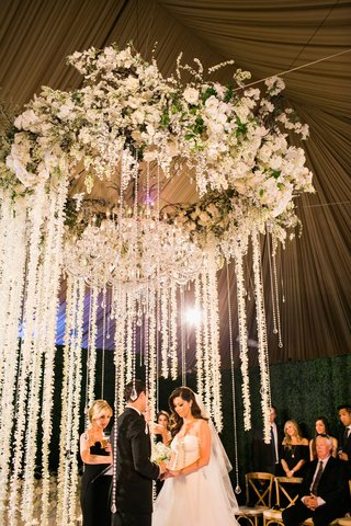 bride-and-groom-exchanging-vows-wedding-ceremony-flower-chandelier-strands-or-orchids-and-crystals