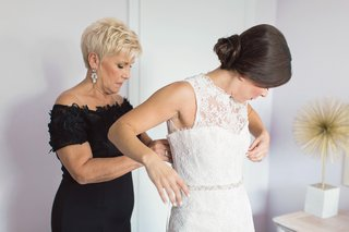bride-in-monique-lhuillier-sleeveless-mermaid-wedding-dress-mother-of-the-bride-in-black-helping