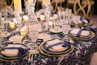 wedding-reception-round-table-pattern-linen-gold-plates-gold-calligraphy-on-navy-blue-ribbon-place