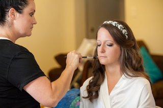 bride-wearing-hairpiece-having-makeup-applied