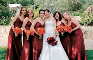 bridesmaids-in-long-red-spaghetti-strap-dresses-and-orange-bouquets