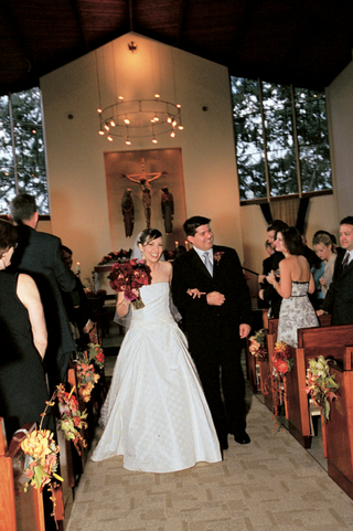bride-and-groom-walk-down-aisle-lined-with-autumn-inspired-flowers