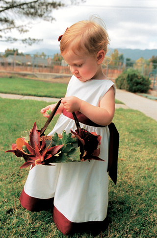 flower-girl-in-white-dress-with-red-trim-carries-basket-lined-with-leaves