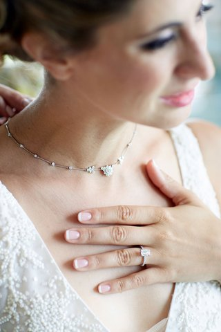 bride-with-emerald-cut-pave-diamond-engagement-ring-and-flower-family-heirloom-necklace