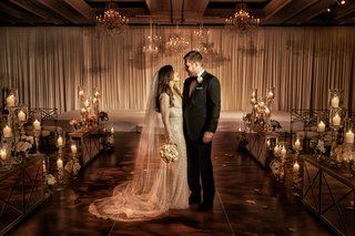 bride-in-inbal-dror-wedding-dress-with-groom-in-ceremony-ballroom-drapery-chandeliers-mirrors-candle