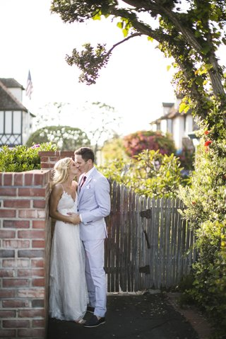 couple-kissing-against-bricks-next-to-wood-gate
