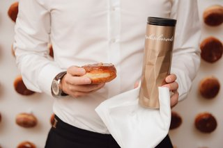 wedding-reception-guest-holding-donut-doughnut-and-coffee-thermos-take-home-favor-late-night-snack