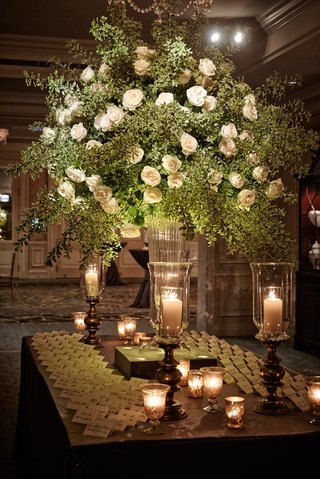 wood-escort-card-table-with-seating-assignments-and-tall-greenery-arrangement-with-white-flowers