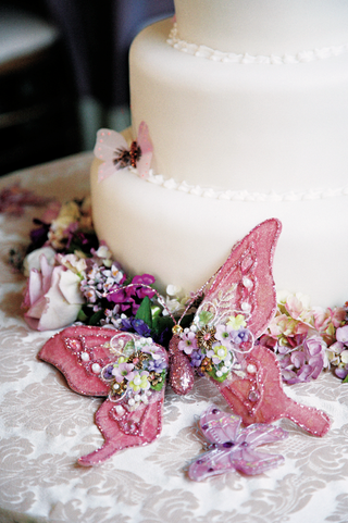 white-wedding-cake-with-pink-and-purple-butterflies-and-colorful-flowers