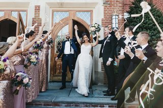 bride-and-groom-celebrating-exiting-the-church-while-bridal-party-waves-streamers