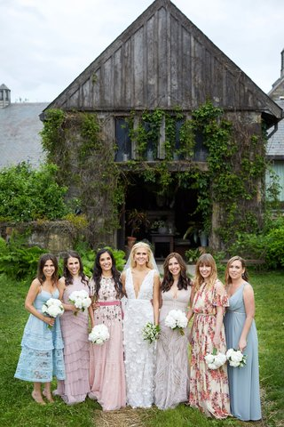 bride-in-deep-v-neck-wedding-dress-marchesa-with-bridesmaids-mismatched-dresses-blue-pink-floral