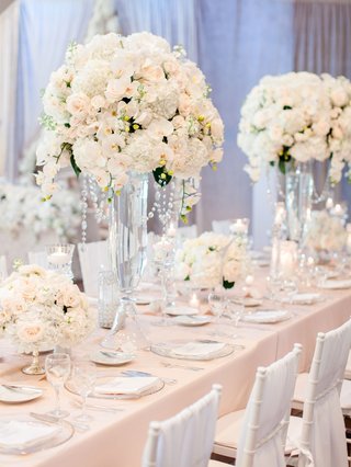 wedding-reception-long-rectangle-table-with-tall-white-centerpieces-and-low-flowers-glass-candles