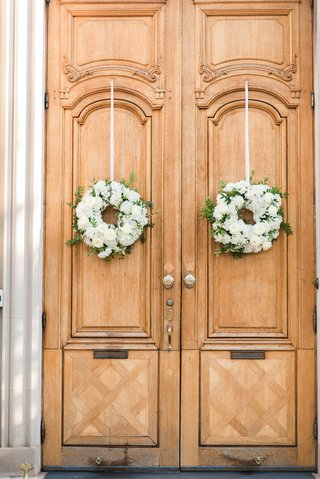 wedding-ceremony-at-the-meridian-house-white-flower-wreaths-on-tall-wood-doors-greenery-ribbon