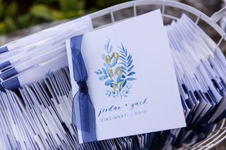 wedding-ceremony-program-details-blue-ribbon-with-calligraphy-and-foliage-program-with-gold-date