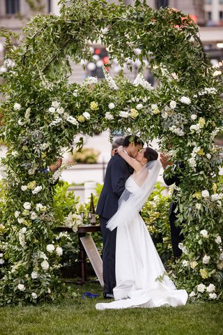 A Charming Fete Romantic Ceremony greenery bride and groom kiss