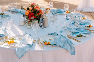 wedding reception round table kumquat blue napkin and colorful pink red centerpiece