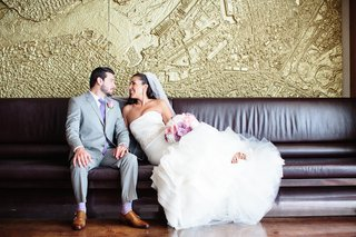 bride-in-a-strapless-fit-and-flare-vera-wang-dress-sits-with-groom-in-grey-suit-purple-tie