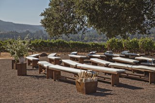 wedding-ceremony-in-wine-country-california-wood-bench-with-white-cushion-parasols-greenery