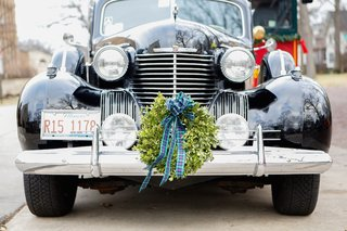 green-wreath-with-blue-bow-on-front-grill-of-black-classic-cadillac-car