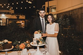 bride-in-givenchy-wedding-dress-short-sleeve-with-groom-cakes-with-orange-flowers-outdoor-reception