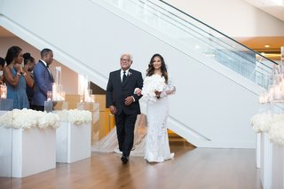 bride walking down aisle with father of bride wood floor aisle riser with white flowers candles