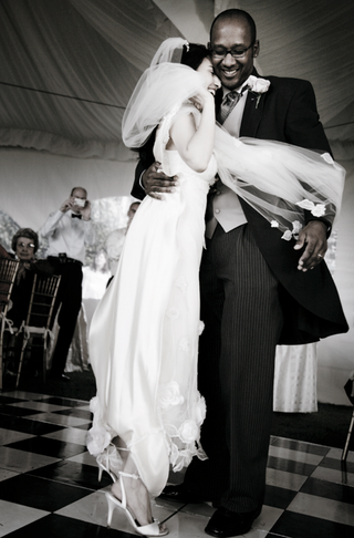 bride-in-a-claire-pettibone-lace-gown-and-veil-dances-with-groom-in-black-tails