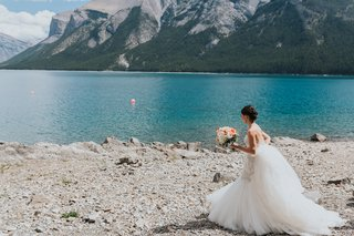 bride-in-watters-mermaid-wedding-dress-with-beaded-bodice-low-updo-lakeshore-of-banff-national-park
