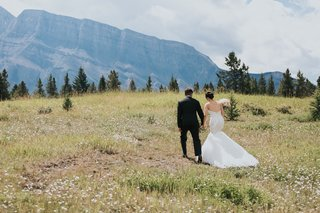 groom-in-ermenegildo-zegna-bride-in-watters-banff-national-park-open-field-mountains