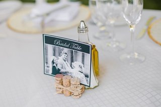 wedding-head-table-with-photo-sign-of-the-bride-groom-and-their-dog-propped-by-wine-corks
