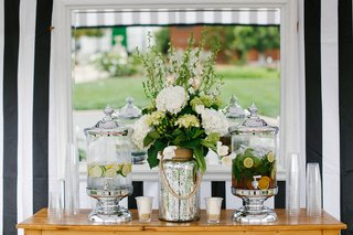 silver-water-dispensers-serving-drinks-at-wedding-ceremony-with-mercury-glass-vase-flowers