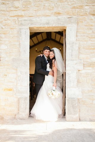 young-bride-in-monique-lhuillier-wedding-dress-and-groom-in-suit-at-chapel-in-texas
