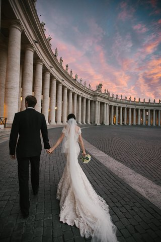 newlyweds-walk-through-historic-building-at-sunset-in-italy