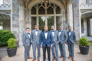 groom-in-navy-brocade-blazer-from-ralph-lauren-and-black-slacks-groomsmen-grey-suits-blue-bow-ties