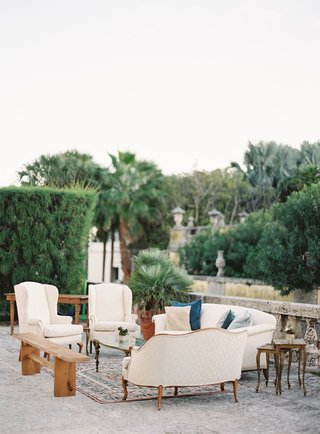 wedding-reception-white-sofa-armchair-settee-wood-bench-on-persian-rug-outdoors-in-garden-venue