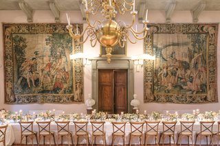 wedding-reception-long-table-wood-vineyard-chairs-tapestry-hanging-on-wall-wood-door-villa-venue