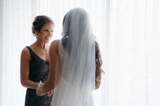 mother-of-the-bride-in-sparkling-embroidery-black-gown-smiling-at-bride