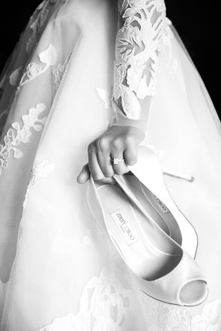 black-and-white-photo-of-bride-carrying-jimmy-choo-peep-toe-pumps