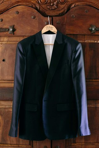 a-grooms-dark-blue-tuxedo-jacket-hanging-up-before-ceremony