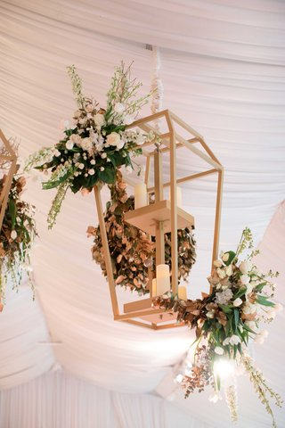 gold-lantern-with-pillar-candle-at-wedding-reception-tent-with-greenery-flowers-over-dance-floor