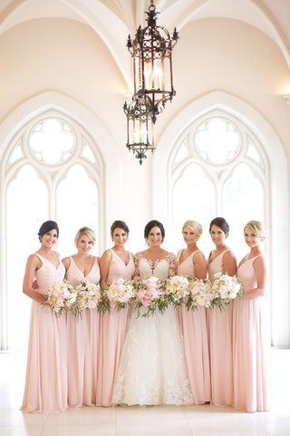bride-in-illusion-long-sleeve-wedding-dress-with-bridesmaids-in-pink-long-dresses-v-neck-flowers