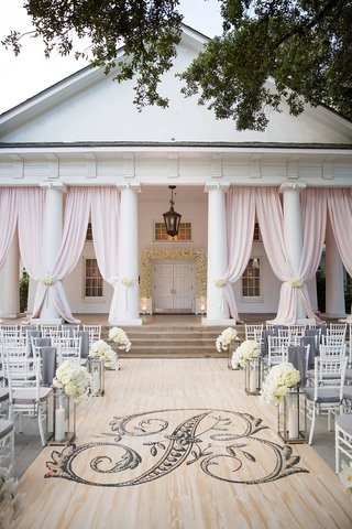 wedding-ceremony-on-porch-with-wood-aisle-runner-pink-drapery-between-columns-white-flowers-chairs